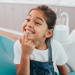 little girl sitting in dental chair and pointing to her teeth