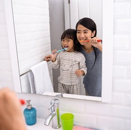 a child and their parent brushing their teeth together