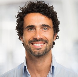 Man smiling in blue collared shirt with curly hair