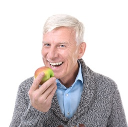 Older man eating apple with implant dentures