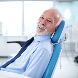 Older man wearing tie smiling in the dental chair