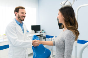 Dentist shaking hands with patient