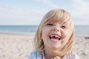 Girl missing tooth at the beach smiles after seeing Hoover children's dentist