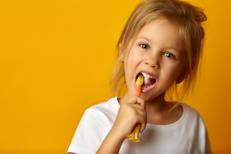 a little girl wearing a white blouse and brushing her teeth with a manual toothbrush