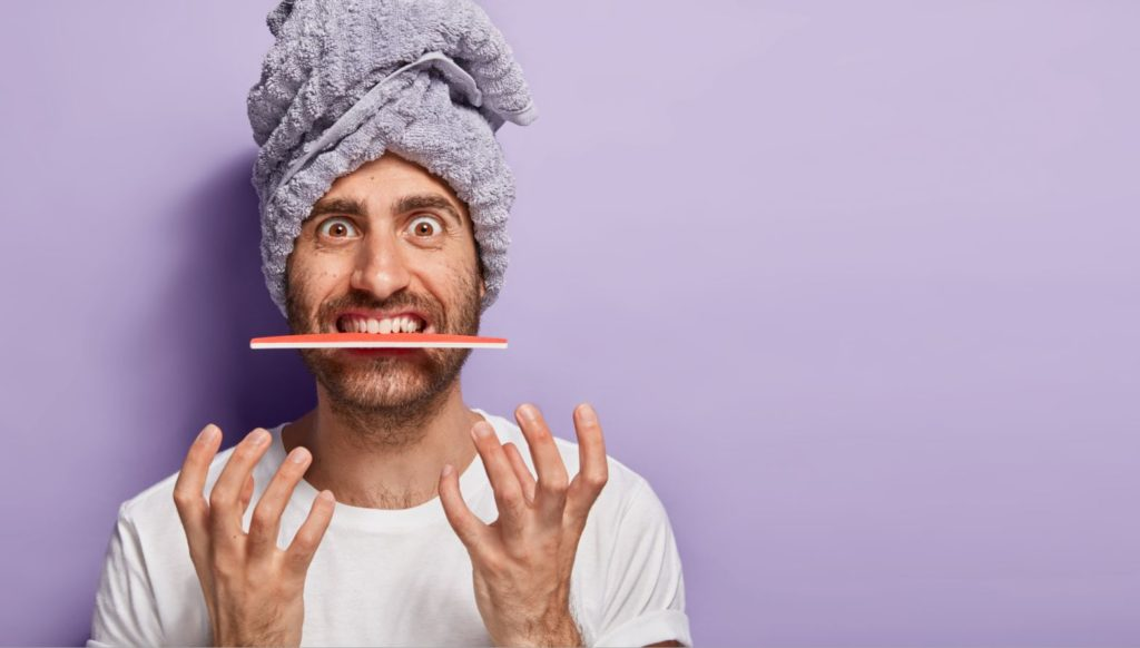 Man with nail file in his mouth
