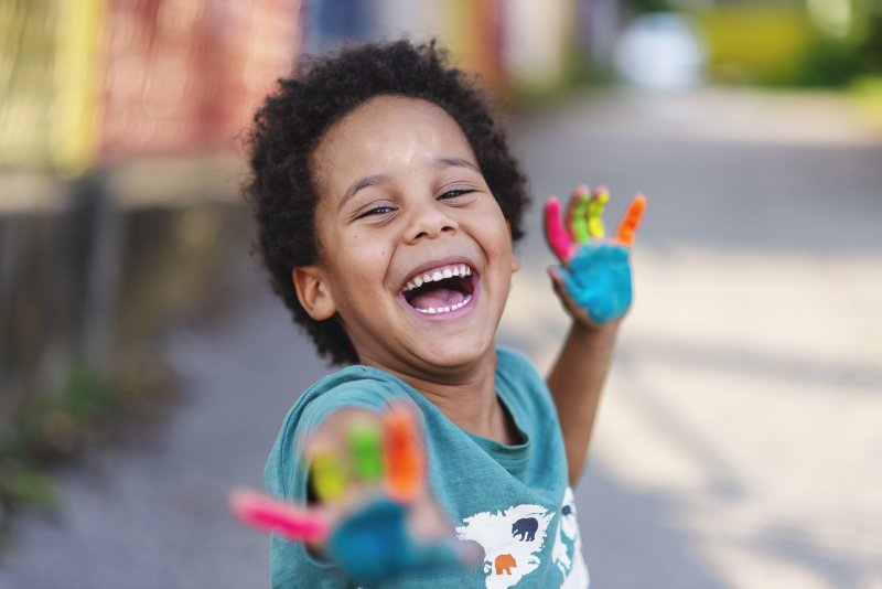young boy smiling with painted hands